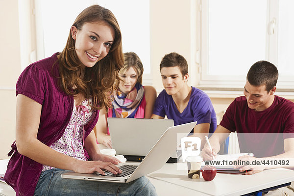 Teenage girl with laptop  students using laptop in background