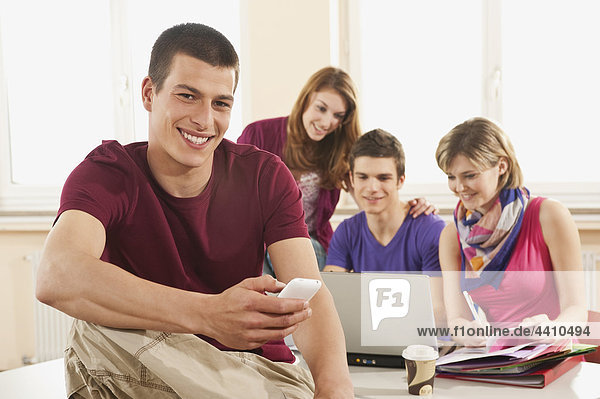 Young man with mobile  students using laptop in background