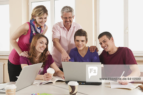 Deutschland  Emmering  Lehrer und Schüler mit Laptop  lächelnd