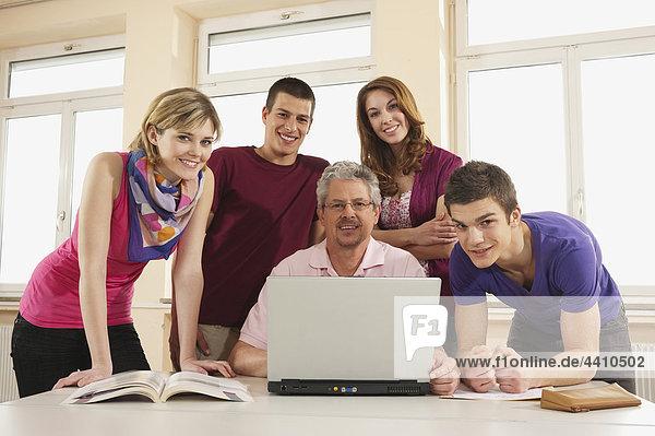 Deutschland  Emmering  Lehrer und Schüler mit Laptop  lächelnd  Portrait