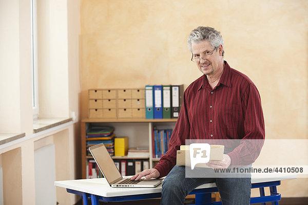 Senior man using laptop  smiling  portrait