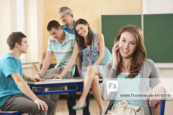 Teenager-Mädchen am Telefon mit Schülern  die den Laptop im Hintergrund benutzen.