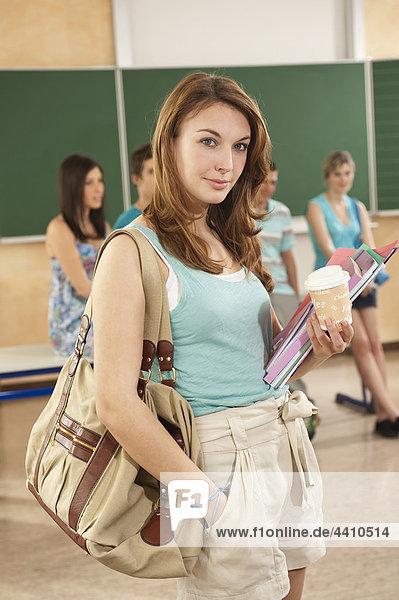 Teenagermädchen lächelt mit Schülern im Hintergrund