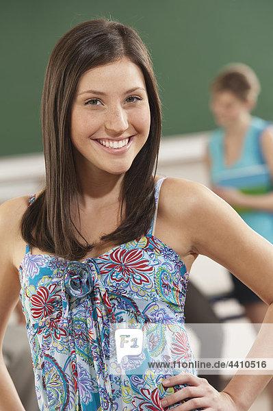 Junge Frau lächelt mit Studenten im Hintergrund