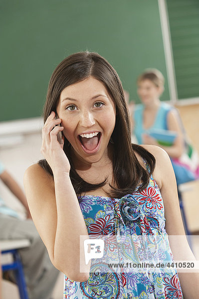 Junge Frau spricht auf dem Handy mit Schülern im Hintergrund