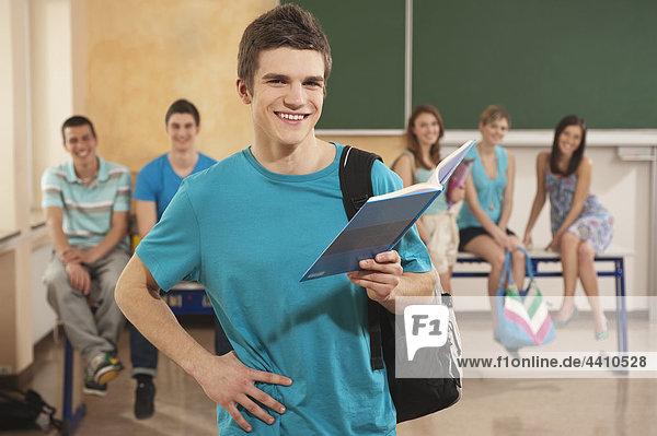 Teenager-Junge hält Buch mit Schülern im Hintergrund