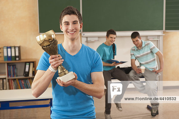 Junger Mann mit einer Trophäe mit Studenten im Hintergrund.