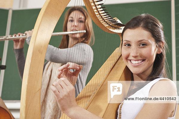 Teenager-Mädchen und junge Frau  die Musikinstrumente spielen