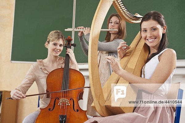 Teenager-Mädchen und junge Frauen  die Musikinstrumente spielen.