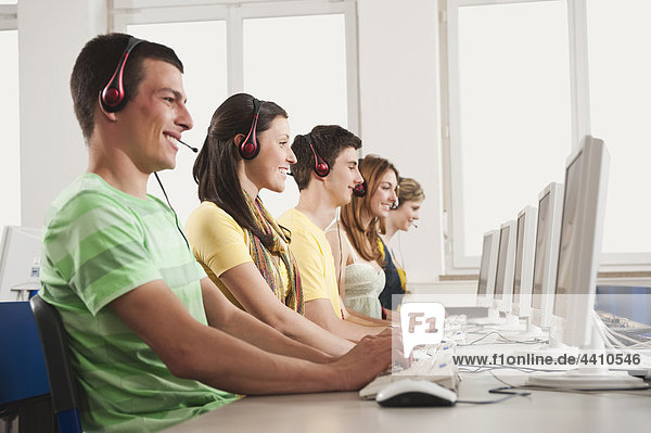 Deutschland  Emmering  Studenten mit Computer im Computerlabor  lächelnd