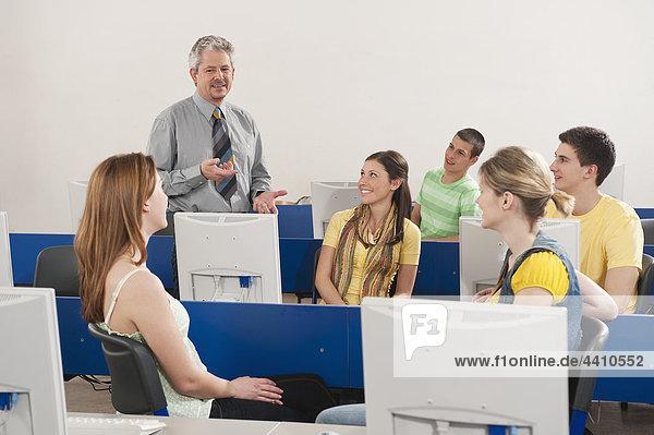 Deutschland  Emmering  Dozent bei der Erläuterung von Studenten im Computerlabor