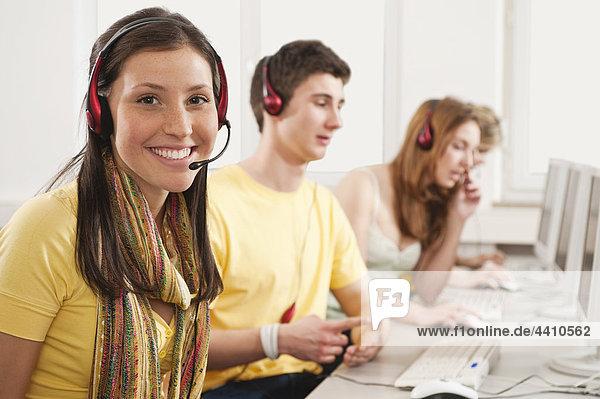 Frau lächelt mit Schülern  die den Computer im Hintergrund benutzen.