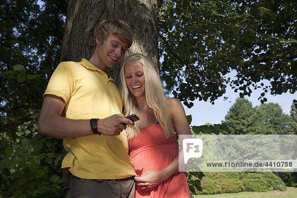 Deutschland  Dortmund  Junges Paar mit Handy und Lächeln