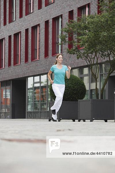 Junge Frau joggt  lächelt.