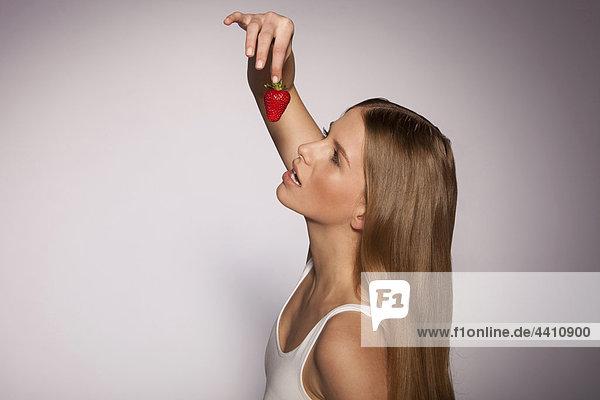 Junge Frau hält Erdbeere