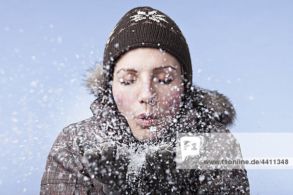 Young woman blowing snow  close-up