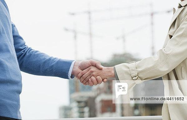 Mann und Frau schütteln sich die Hände.