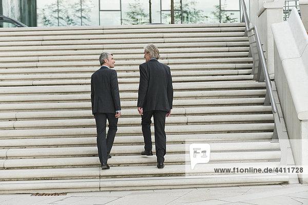 Deutschland  Hamburg  Geschäftsleute klettern gemeinsam auf Stufen