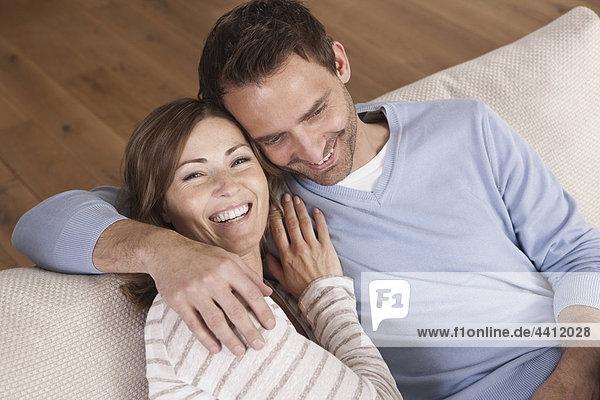 Deutschland  Paar auf Couch sitzend  lächelnd