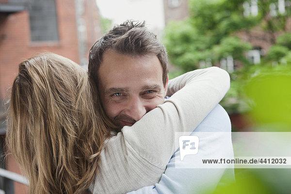 Deutschland  Paarumarmung auf dem Balkon  Mann lächelnd