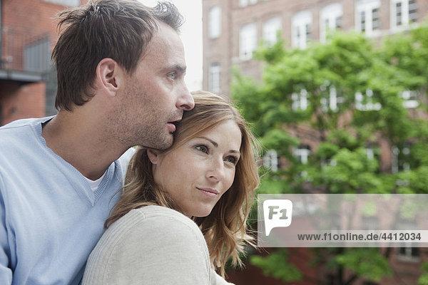Deutschland  Paar auf dem Balkon entspannen  wegschauen