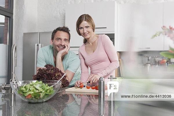 Deutschland  Paar Zubereitung Salat in der Küche  lächelnd  Portrait