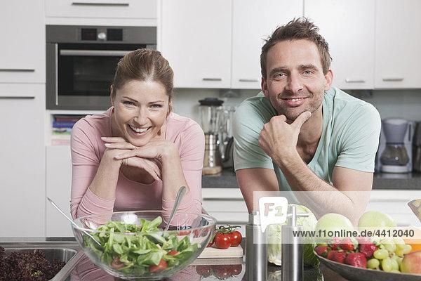 Deutschland  Paar mit Gemüse und Obst auf Küchenarbeitsplatte  lächelnd  Portrait