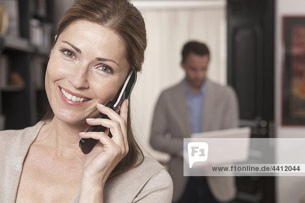 Deutschland  Frau am Telefon mit Mann im Hintergrund