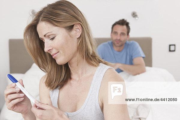 Deutschland  Frau liest Schwangerschaftstestergebnisse mit Mann im Hintergrund