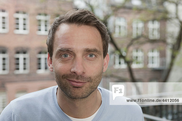 Deutschland  Porträt eines Mannes auf dem Balkon  lächelnd