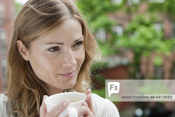 Deutschland  Frau hält Kaffeetasse und schaut weg  lächelnd