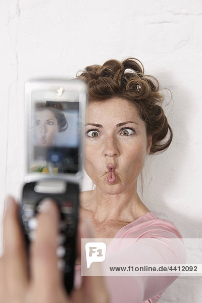Deutschland  Frau fotografiert sich mit dem Handy