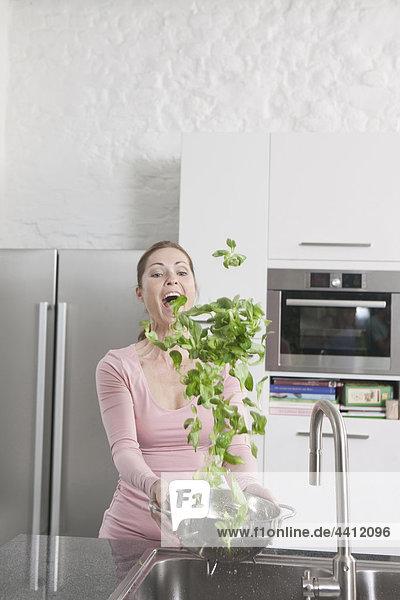 Deutschland  Frau wäscht Gemüse in der Küche