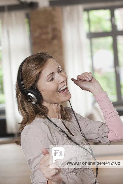 Deutschland  Nahaufnahme einer Frau beim Musikhören