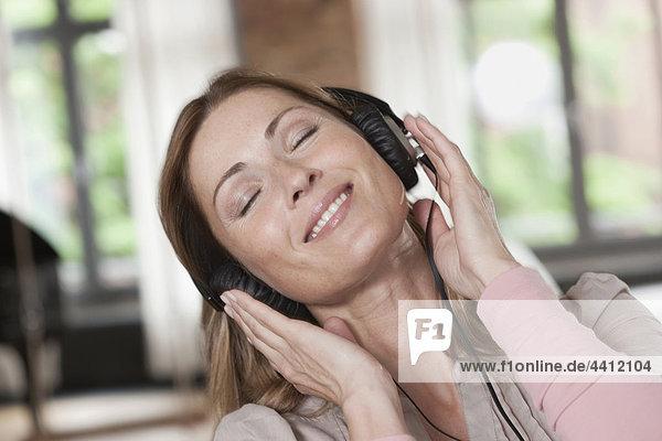 Deutschland  Nahaufnahme einer Frau  die Musik hört  lächelnd