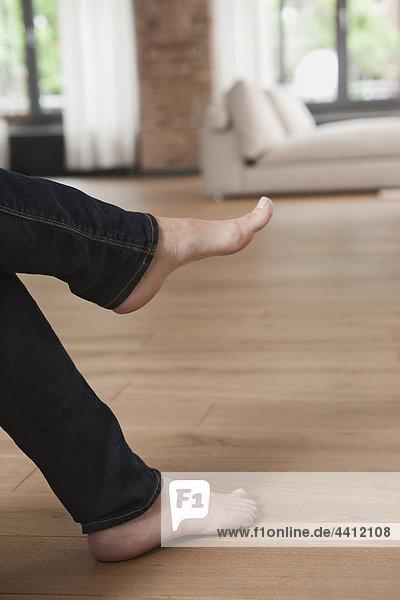 Deutschland  Frauenfüße mit Sofa im Hintergrund