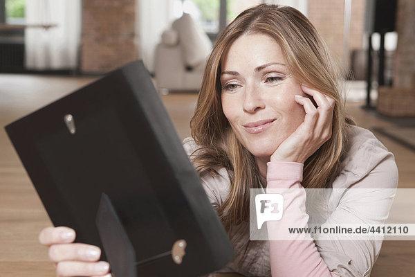 Deutschland  Frau liegt und schaut Fotorahmen  lächelndDeutschland  Frau liegt und schaut Bilderrahmen an  lächelnd
