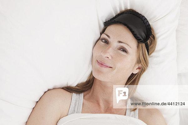 Deutschland  Frau auf Bett mit Augenmaske