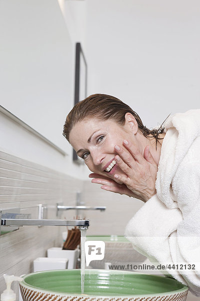 Deutschland  Frau wäscht Gesicht  lächelnd  Portrait