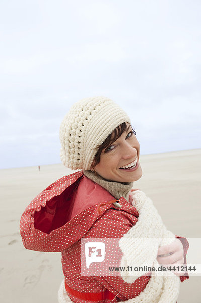 Germany  St Peter-Ording  North sea  Woman having fun in sand dunes  smiling  portrait