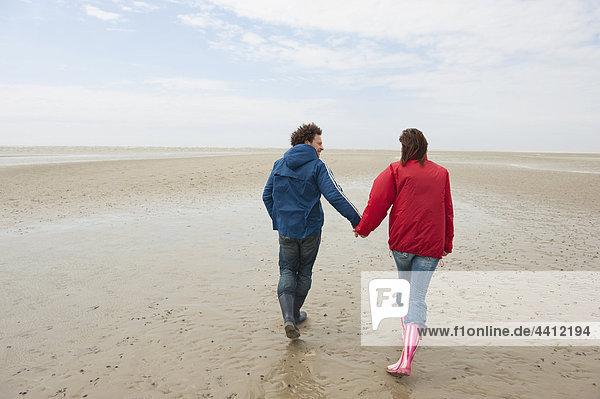 Deutschland  St. Peter-Ording  Nordsee  Paar Händchen haltend und am Strand spazierend