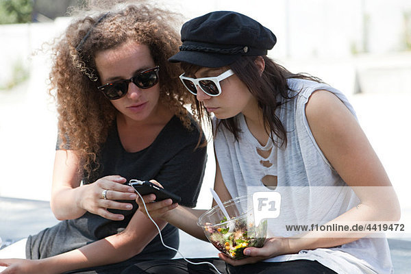 Friends looking at mp3 player