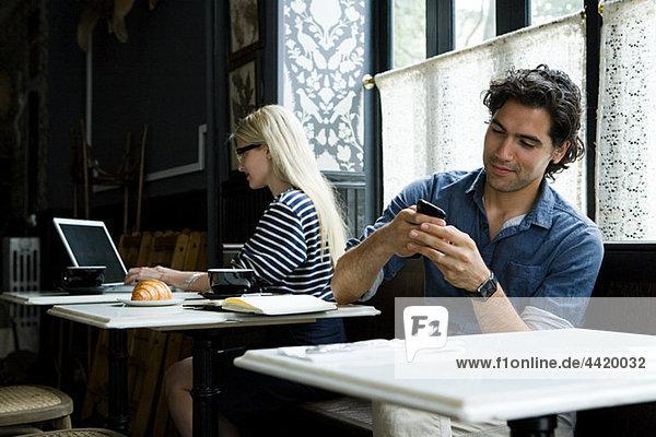 Mann mit Handy und Frau mit Laptop im Cafe
