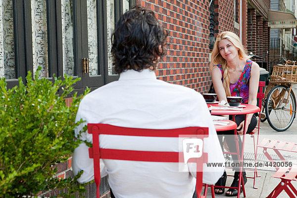 Pärchen beim Kaffeetrinken außerhalb des Cafés