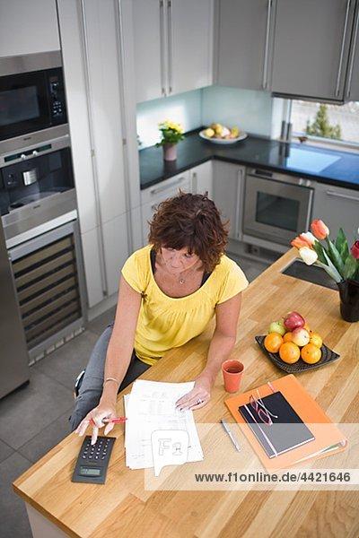 Frau sitzen und Berechnung in Küche