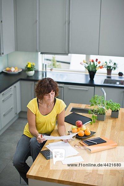 Frau sitzt in Küche mit Rechnungen