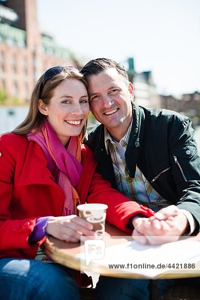 Portrait of couple drinking at outdoor cafe in city