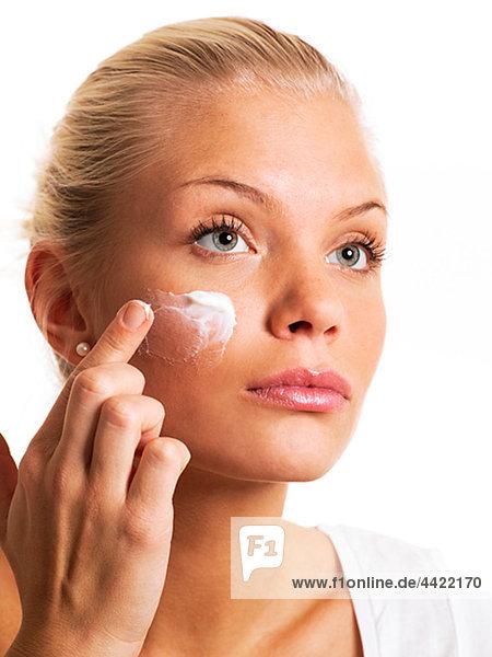Young Frau trägt Sonnencreme auf Gesicht  Nahaufnahme auf