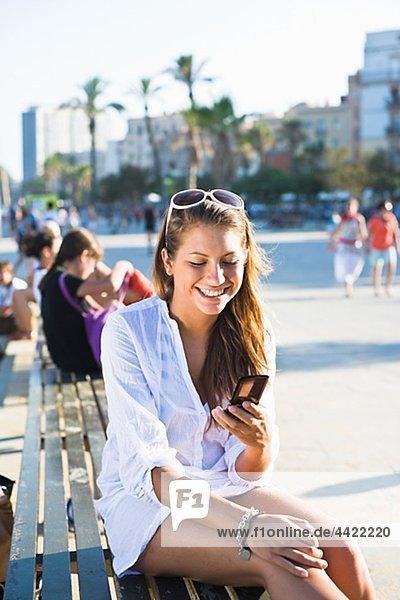 Mädchen sitzen auf Parkbank  mit Handy