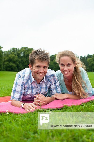 Mid adult couple lying on blanket and looking at camera
